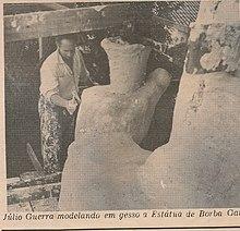 Recorte de jornal com imagem de Júlio Guerra fazendo reparos na mão da estátua de Borba Gato, um dos monumentos de São Paulo.