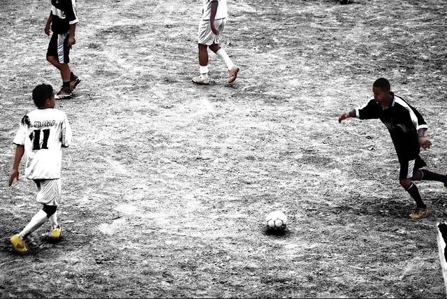 Garotos jogando futebol de várzea em campo de areia