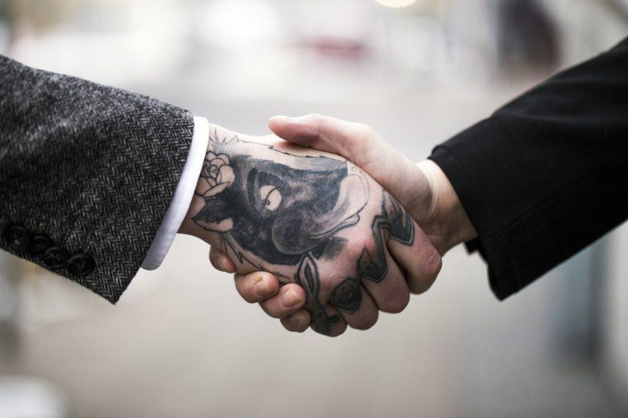 Aperto de mão entre duas pessoas, uma com tatuagem na mão e outra sem