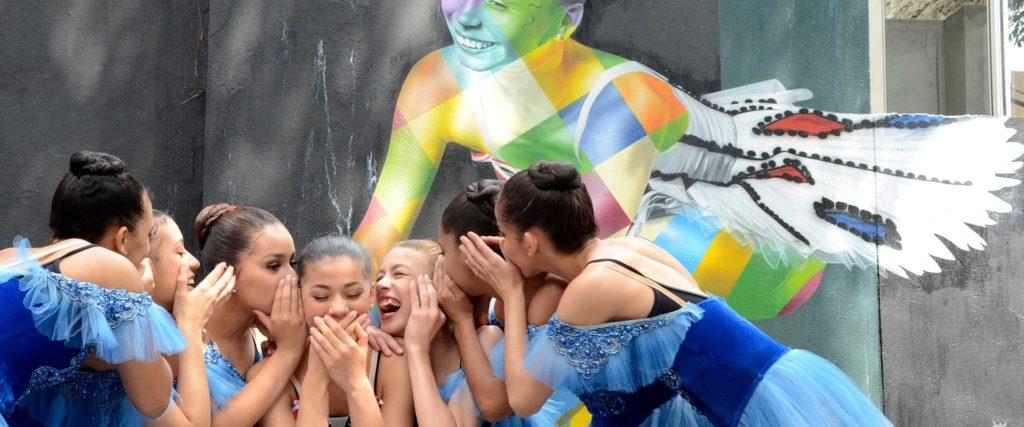 Alunas da ONG Ballet Paraisópolis posam para foto trajando colãs e tutus azuis. Atrás delas há um muro com um grafite de uma bailarina.