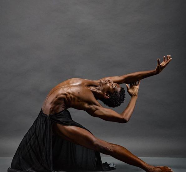 Luís Fernando, ex-aluno da companhia Vidançar, executa um passo de balé durante um ensaio fotográfico. O dançarino está sem camisa e utiliza apenas uma saia preta.