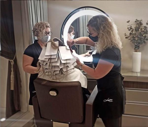 Imagem com pessoas tingindo o cabelo de uma cliente. Nessa imagem, as funcionárias estão de máscara sob um anel de luz.