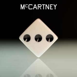 capa do album com um dado apontando para a face de numero três. fundo preto em gradiente