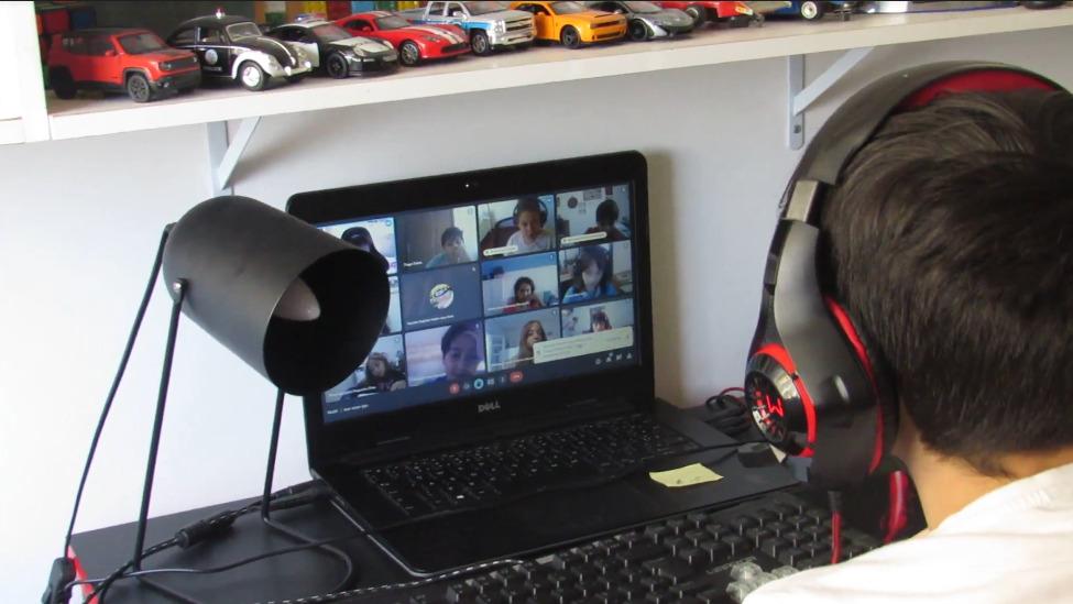 #ParaTodosVerem: Criança utilizando fone, sentada em frente ao computador durante aula online. Na tela do computador podem ser observados outros colegas de sala.
