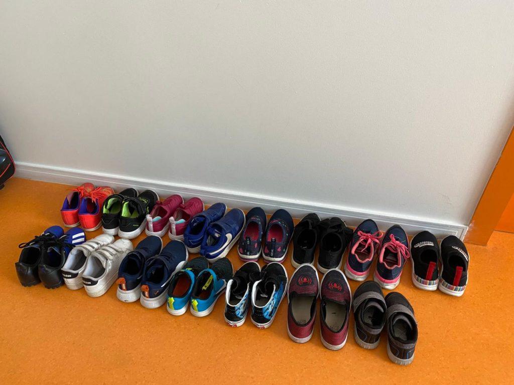 #ParaTodosVerem: sapatos infantis enfileirados no chão laranja de uma sala de aula. As crianças devem retirar os sapatos antes de entrar na classe.