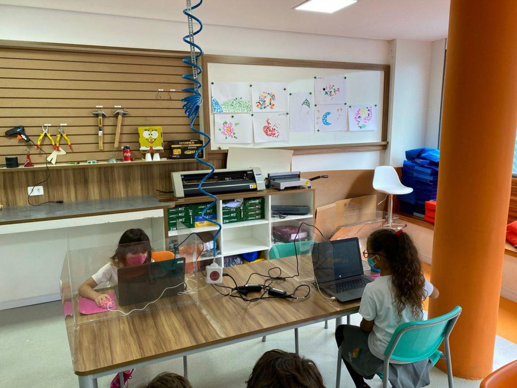 #ParaTodosVerem: Duas crianças sentadas olhando para o computador enquanto estudam. Separadas por placas de acrílico e utilizando máscaras.