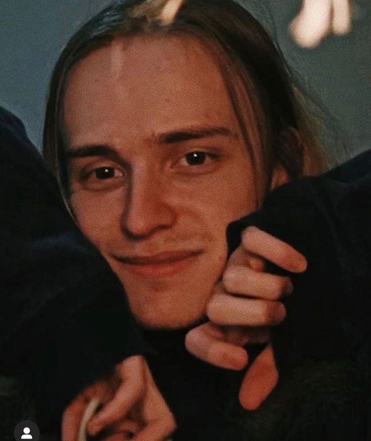 homem branco loiro com a mão no rosto