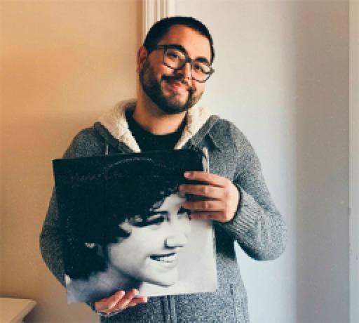 homem sorrindo segura capa de disco de vinil